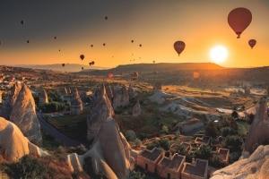 Luchtballonnen zweven boven de aardpiramides van Cappadocië