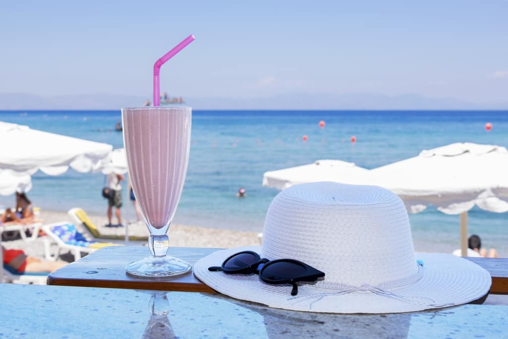 Milkshake, hoed en zonnebril aan het strand
