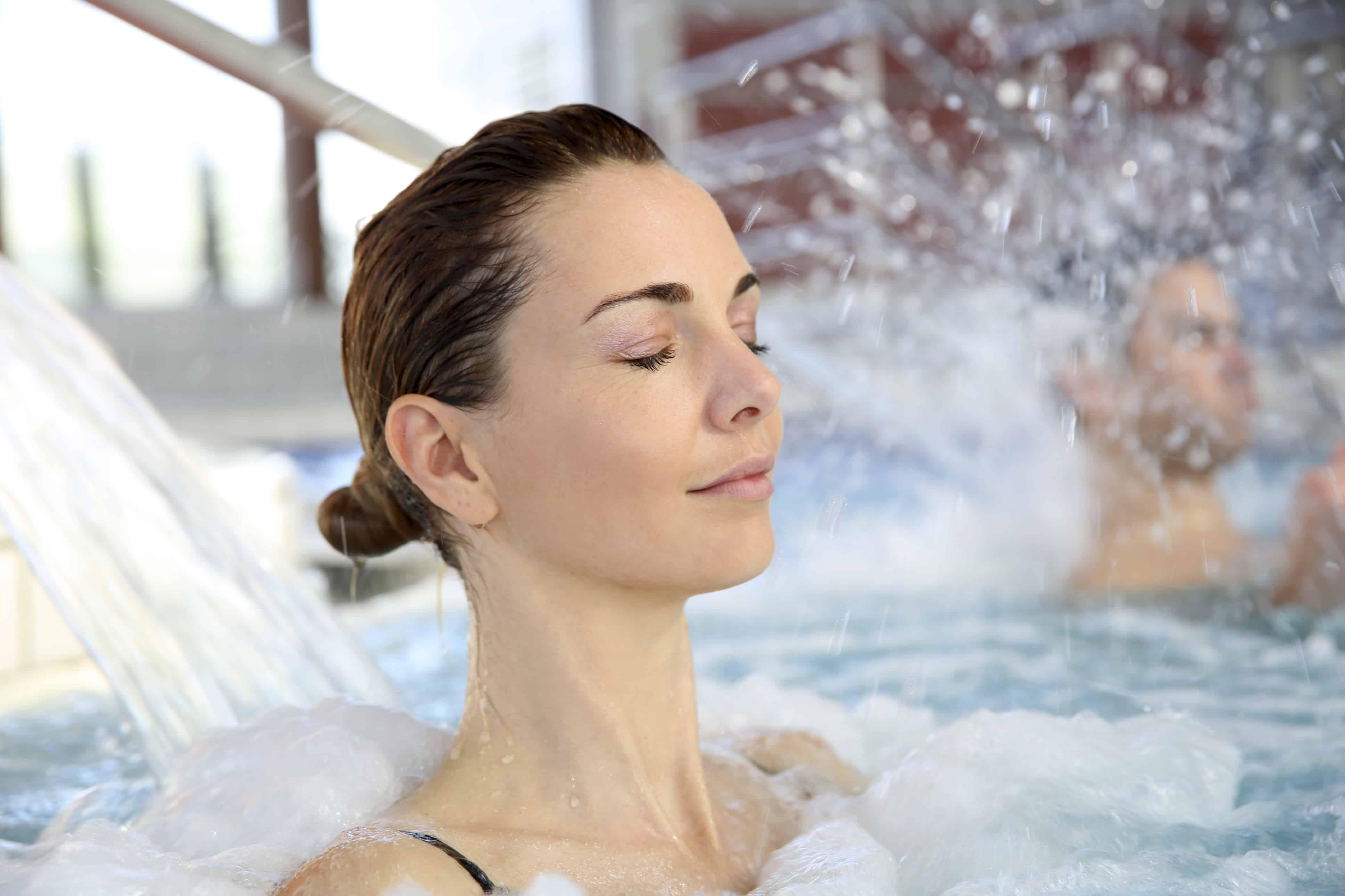 Vrouw geniet van hydrojet in het zwembad