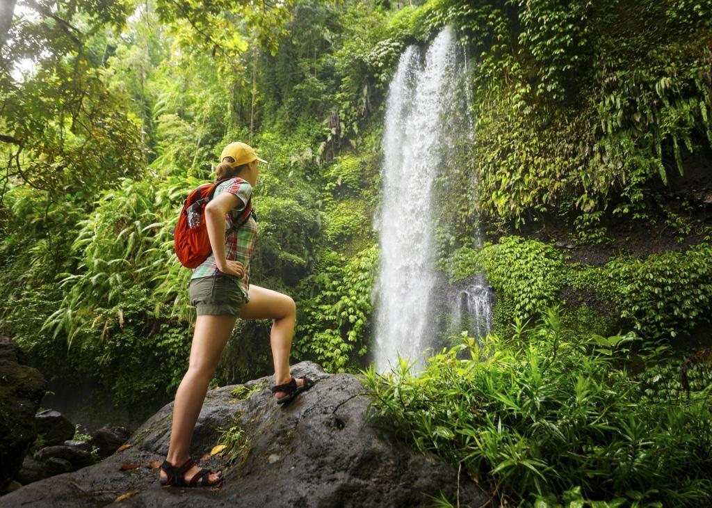 Vrouw staat bij een waterval op Lombok, Indonesië