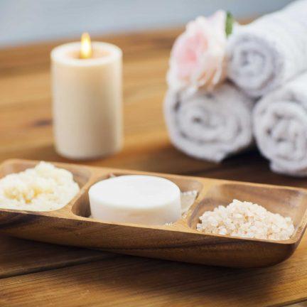 Close-up van zeep, zout en scrub bij een kaars en handdoeken
