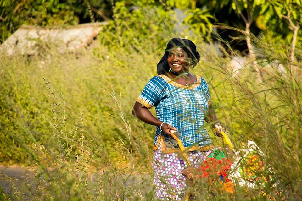 Gambiaanse vrouw met een kruiwagen vol pinda's