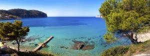 Uitzicht over zee met bomen, rotsen en een boot op Mallorca