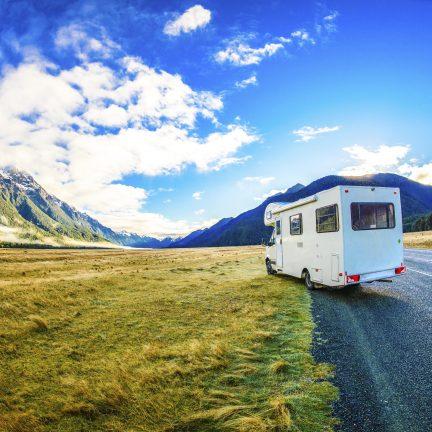 Uitzicht op de bergen met een camper op de weg in Nieuw-Zeeland