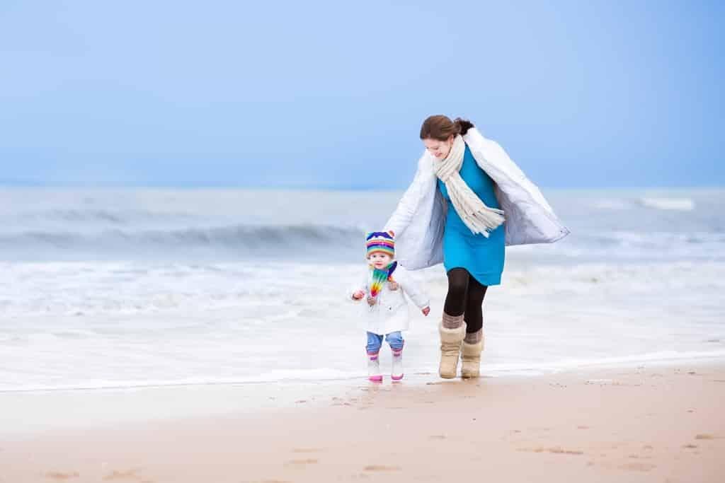 Moeder en dochter op het strand in de winter