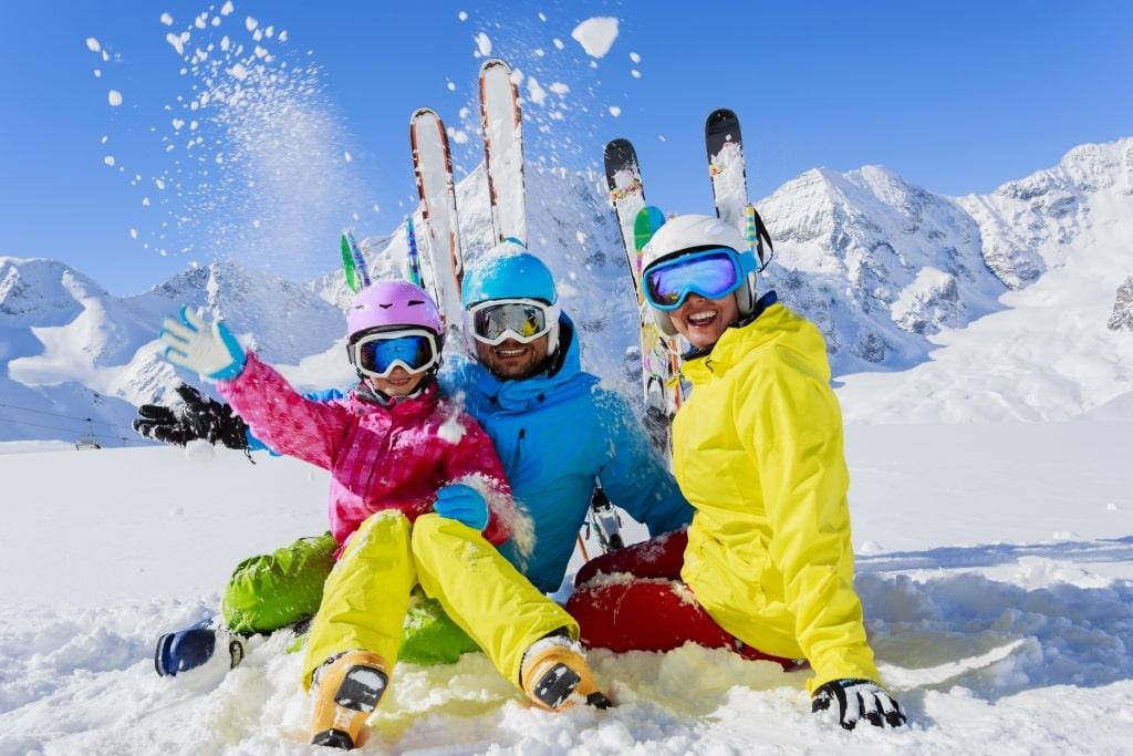 Familie geniet in de sneeuw van hun wintersport