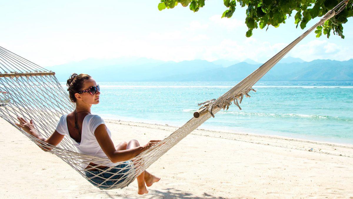 Meisje relaxt in een hangmat op het strand van Bali