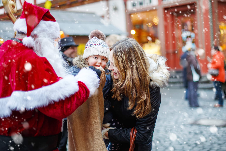 Kerstman en moeder met kind op een kerstmarkt