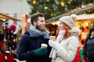 Man en vrouw met warm drinken op een kerstmarkt