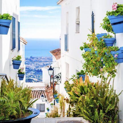 Straat met witte huizen en bloemen in Malaga, Spanje