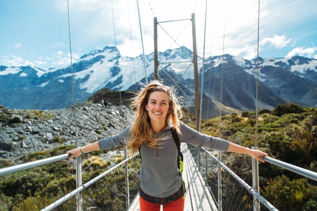 Vrouw op hangbrug in Nieuw-Zeeland