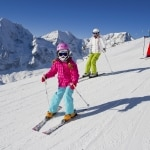 Familie aan het skiën van een skipiste