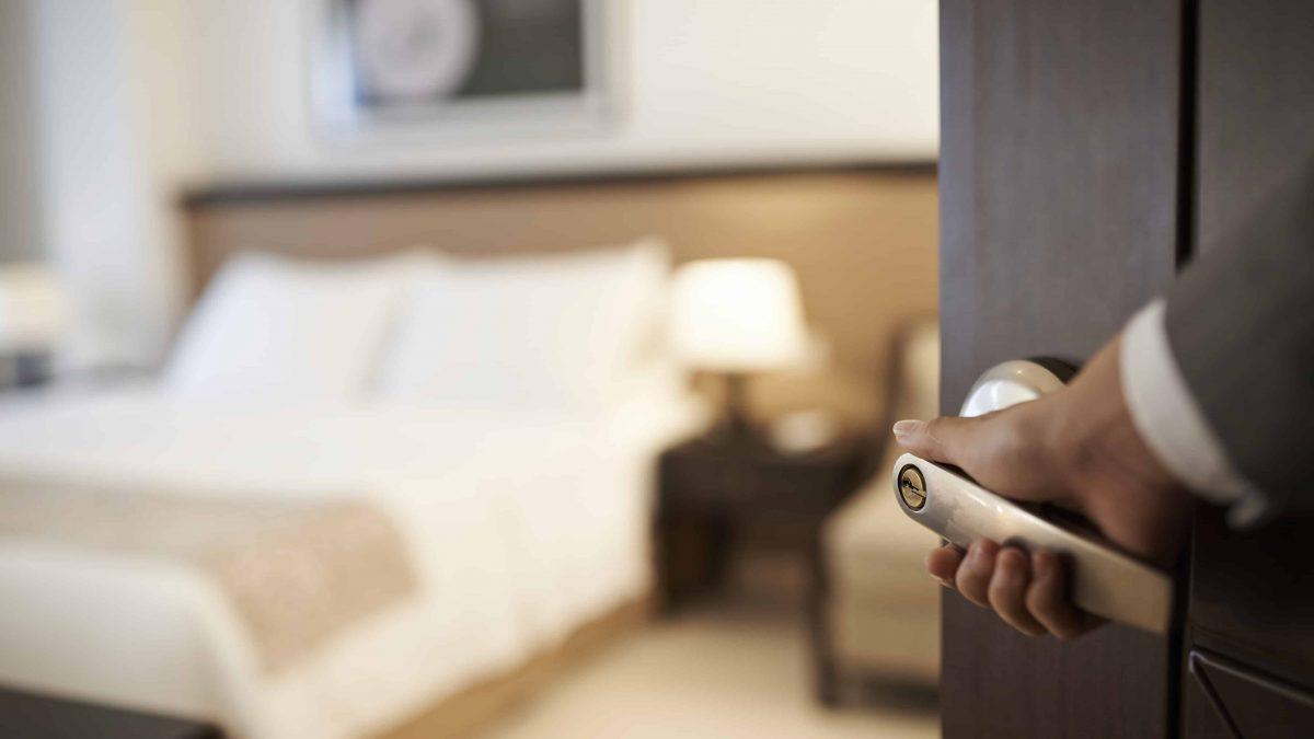 Een hotelmedewerker opent de deur van een hotelkamer
