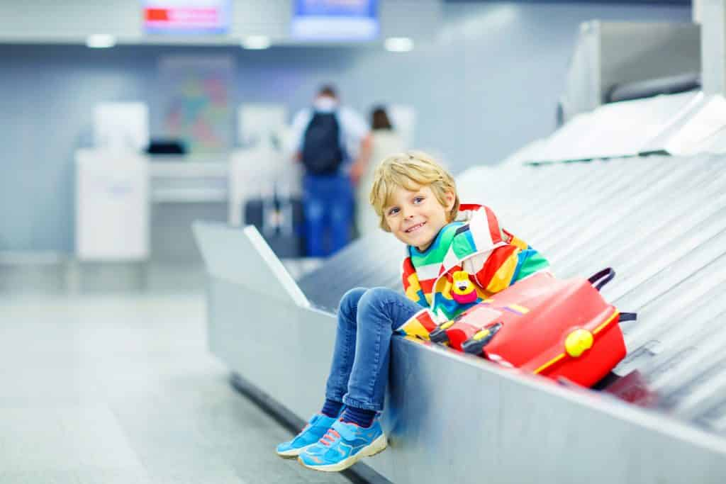 Kind op bagageband van een vliegveld