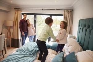 Ouders met kinderen die springen op het bed in een hotel