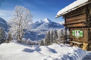 Uitzicht over besneeuwde bergen met bomen en een huisje