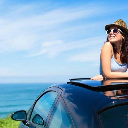 Vrouw staat in een open dakraam van een auto