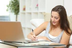 Vrouw schrijft op een notitieblok bij een laptop