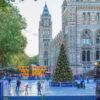 IJsbaan en kerstmarkt voor het Natural History Museum in Londen met uitzicht op de Big Ben