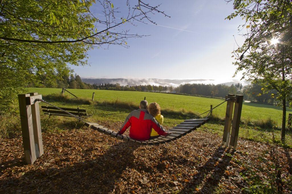 Man en vrouw in een hangmat kijkend naar het landschap van Sauerland, Duitsland