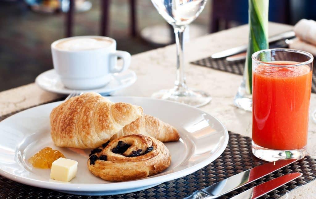 Ontbijt met croissiant, broodje en sap
