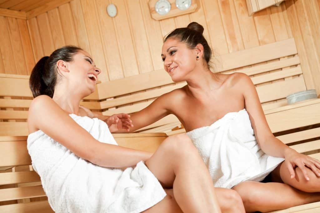 Twee vrouwen lachen in een sauna
