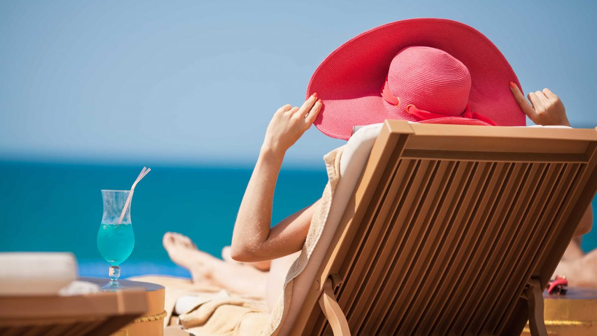 Vrouw met hoed op een strandstoel aan zee