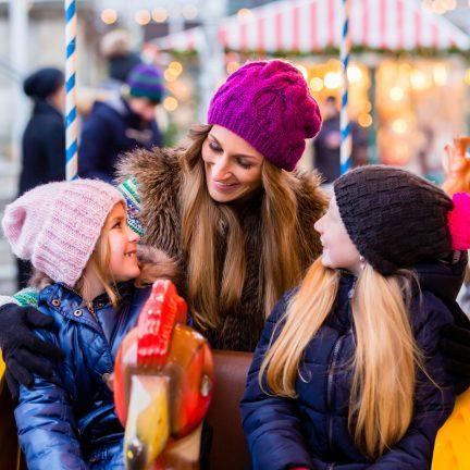 Vrouw met kinderen in een draaimolen op de kerstmarkt