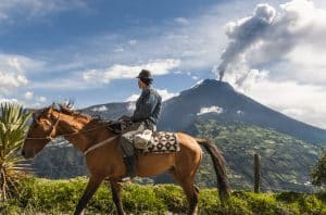 Man op paard met uitzicht op de Tungurahua vulkaan in Ecuador