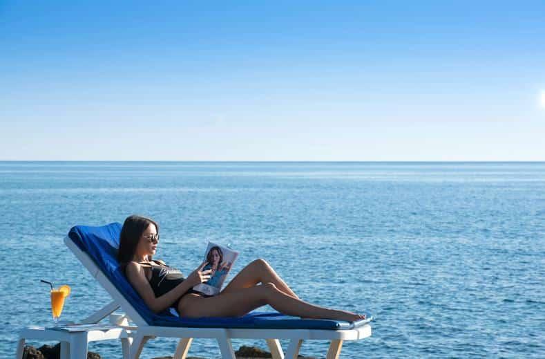 Vrouw ligt op het strand van Silva Beach Resort in Chersonissos, Kreta