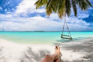 Voeten en hangmat in palmboom met uitzicht op zee