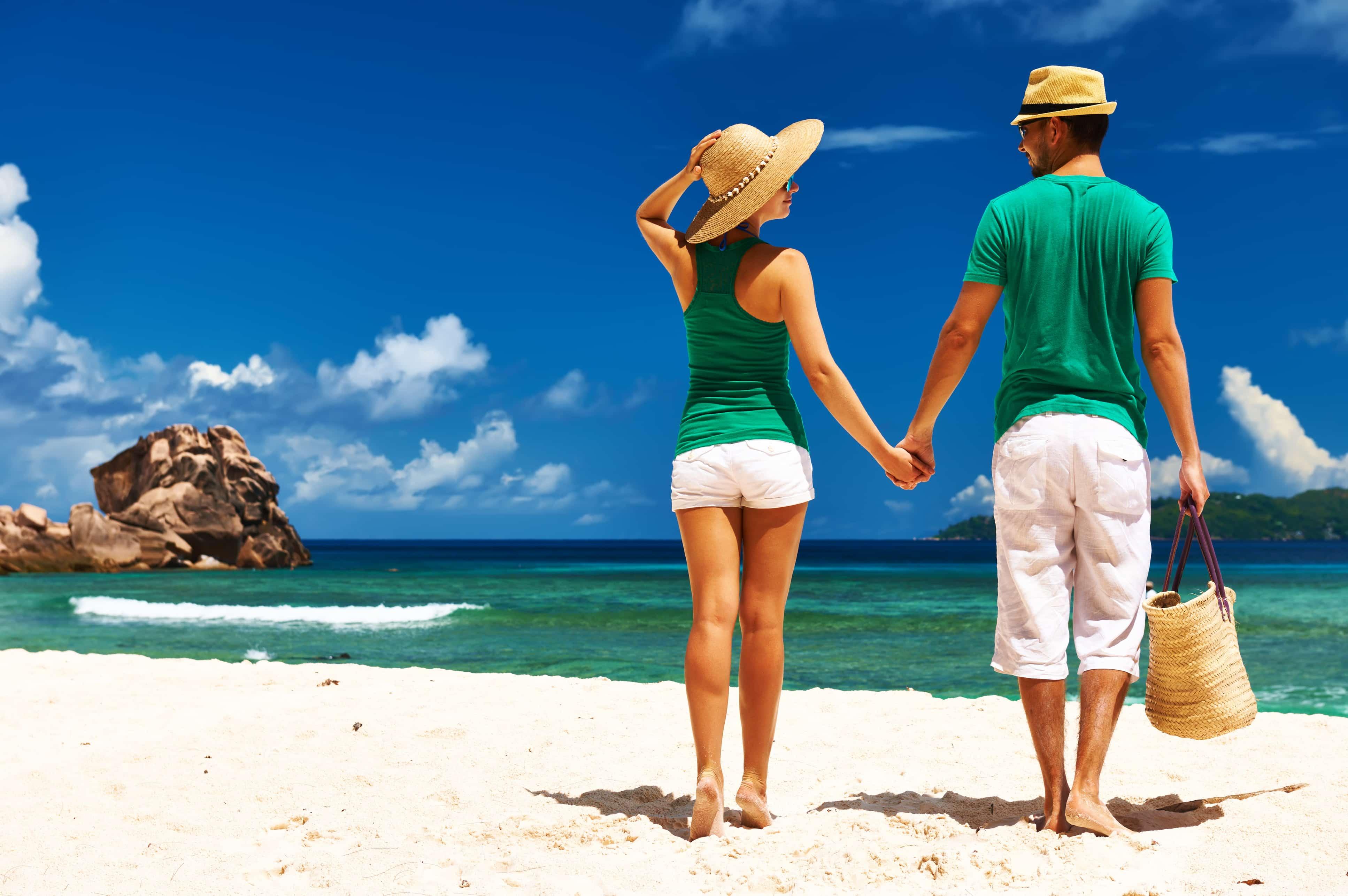 Vrouw en man hand in hand op het strand