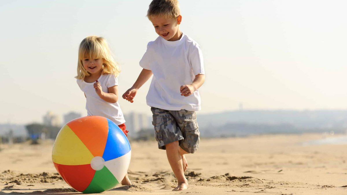 twee kinderen spelen met een strandbal op het strand