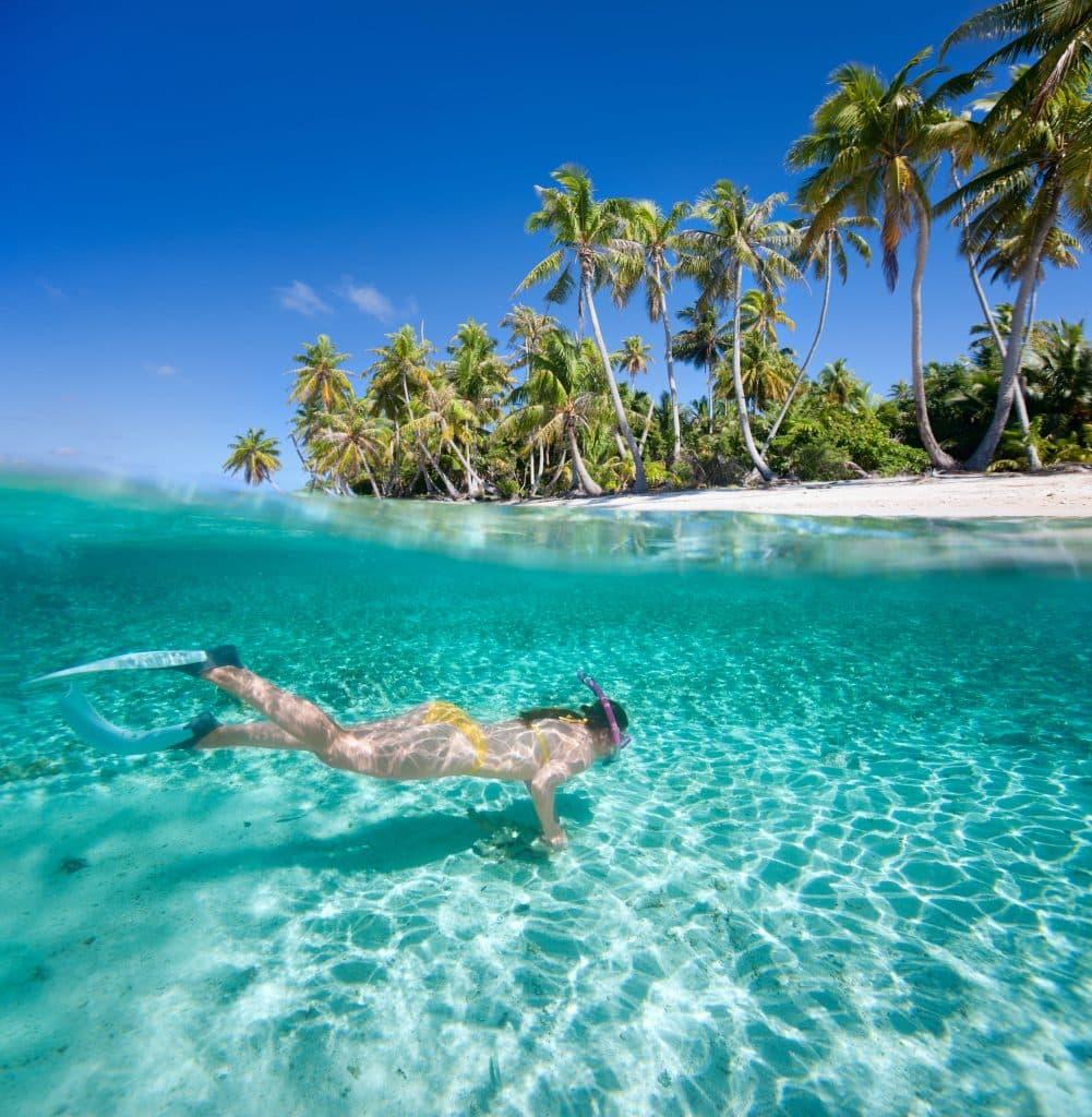 Vrouw aan het snorkelen onder water bij een tropisch eiland