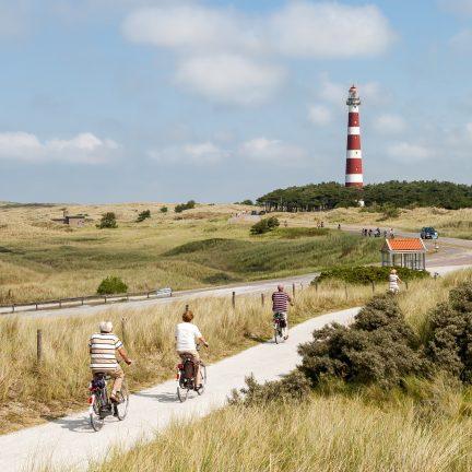 Mensen aan het fietsen bij de vuurtoren van Ameland