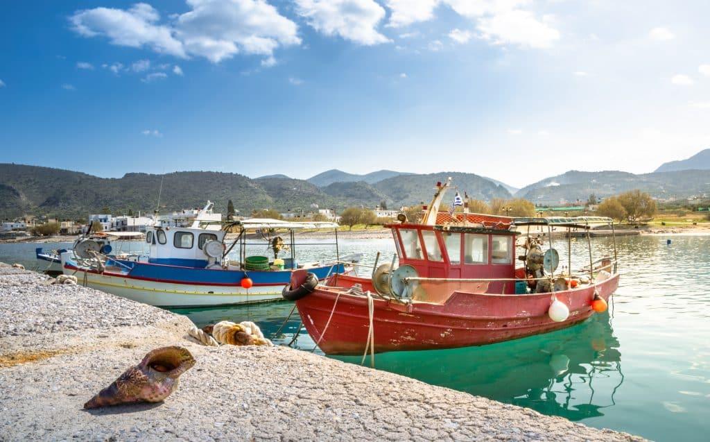 Traditionele vissersboten en schelpen in de haven van Milatos, Kreta, Griekenland