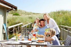 Familie buiten aan het eten bij hun vakantiehuisje