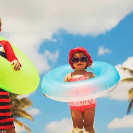 Kleine jongen en meisje met zwembanden om
