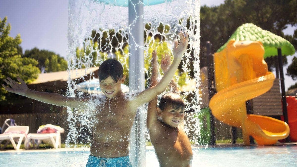 Blije kinderen onder een waterfontein