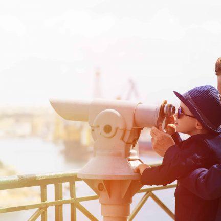 vader en zoon kijken door een verrekijker in een stad