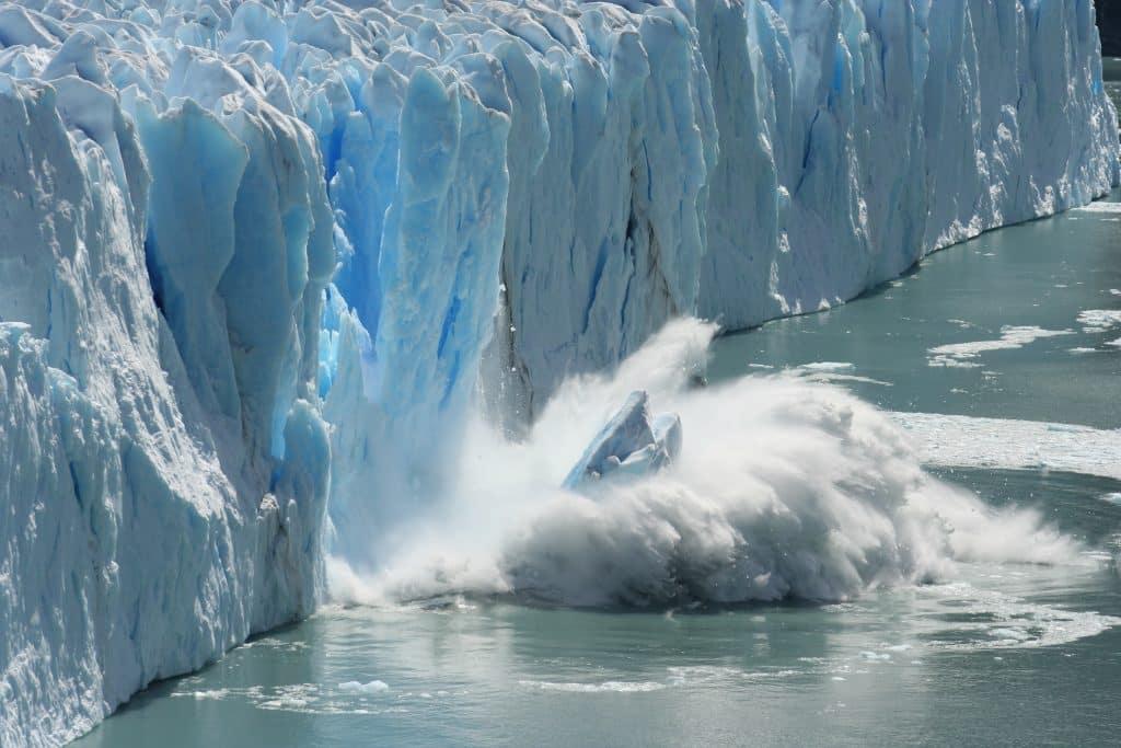 Stuk ijs valt in het water op Antarctica
