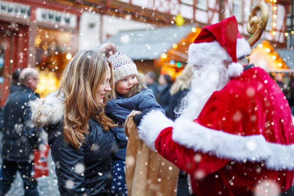 Schattig meisje met haar moeder en de kerstman op de kerstmarkt van munster in duitsland