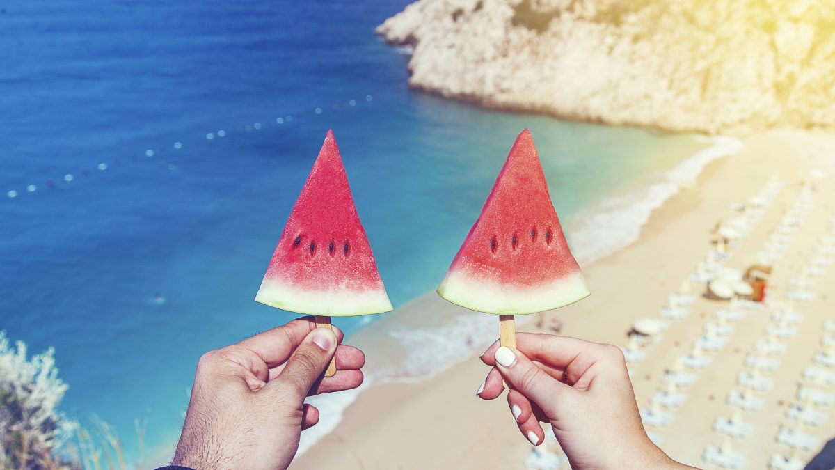 twee watermeloenen stokje strand zee uitzicht