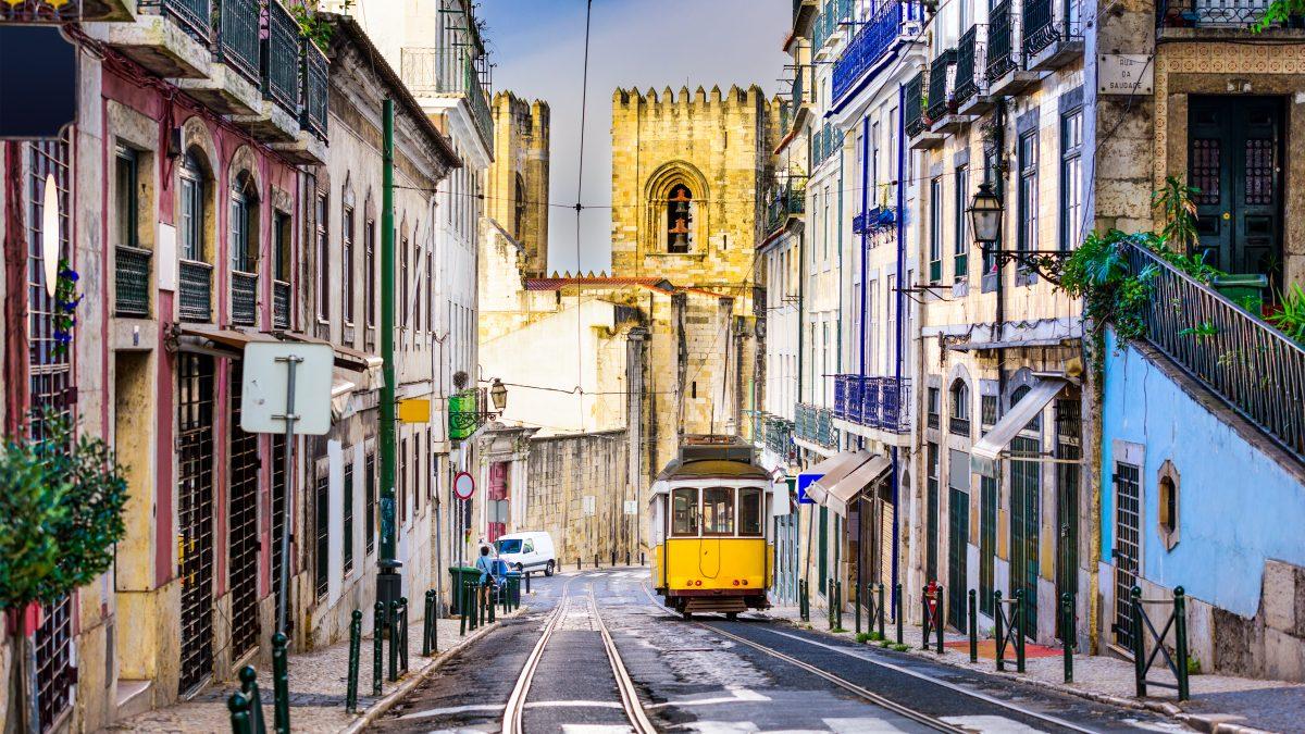 Tram tussen huizen met toren op de achtergrond in Lissabon, Portugal