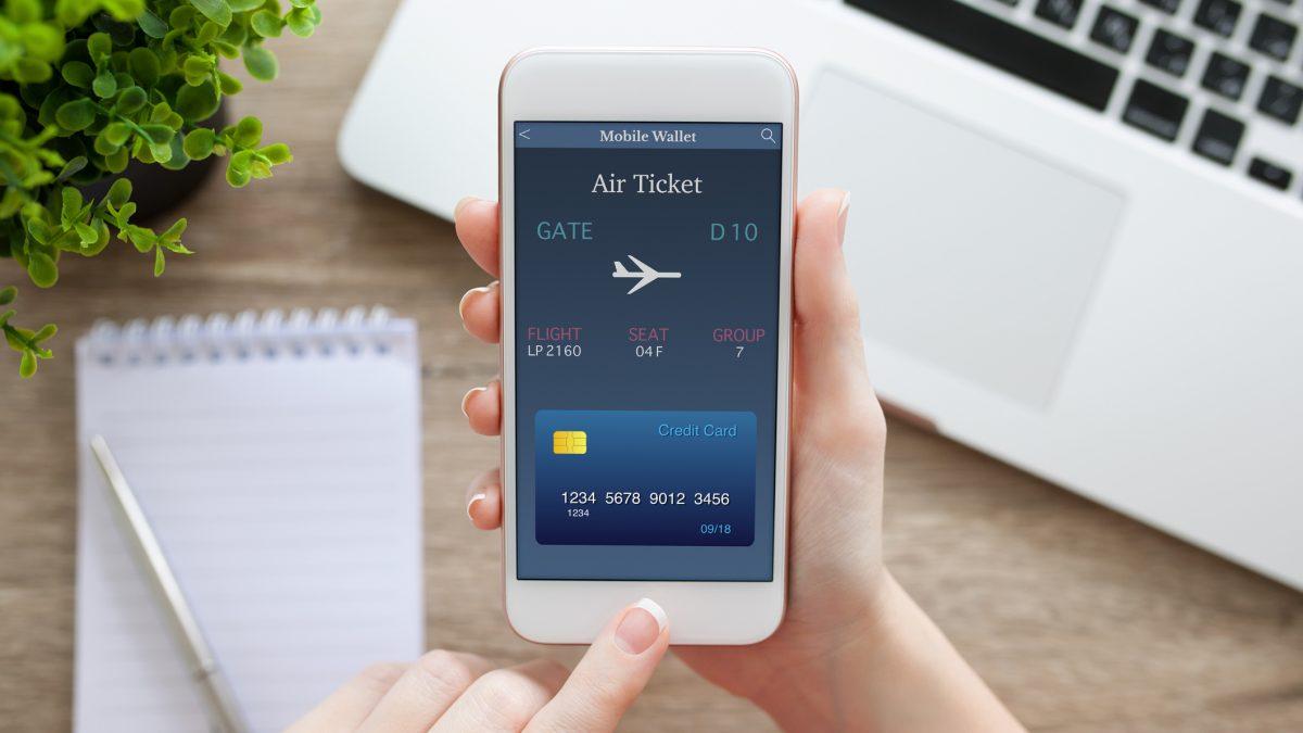 Telefoon met vliegticket en laptop op een bureau