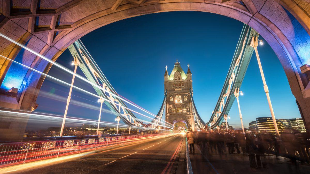 Mensen lopen 's avonds over de verlichte Tower Bridge in Londen, Engeland