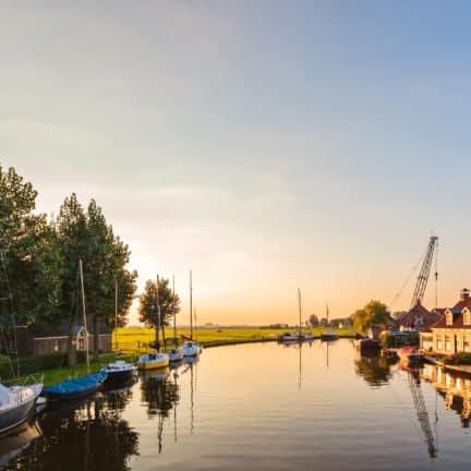 Rivier met zeilboten in Friesland