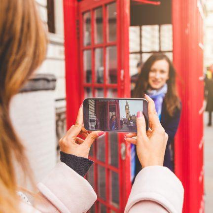 Vriendinnen maken een foto bij een telefooncel in Londen, Engeland