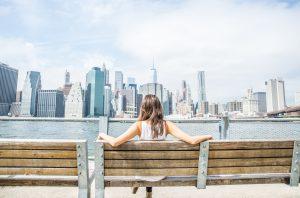 Vrouw op een bankje kijkt uit over de skyline van New York