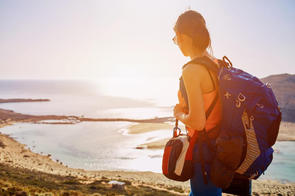 Vrouw met rugzak kijkt uit over Balos beach op Kreta, Griekenland
